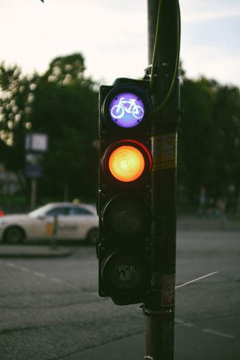 Illuminated road sign on street in city