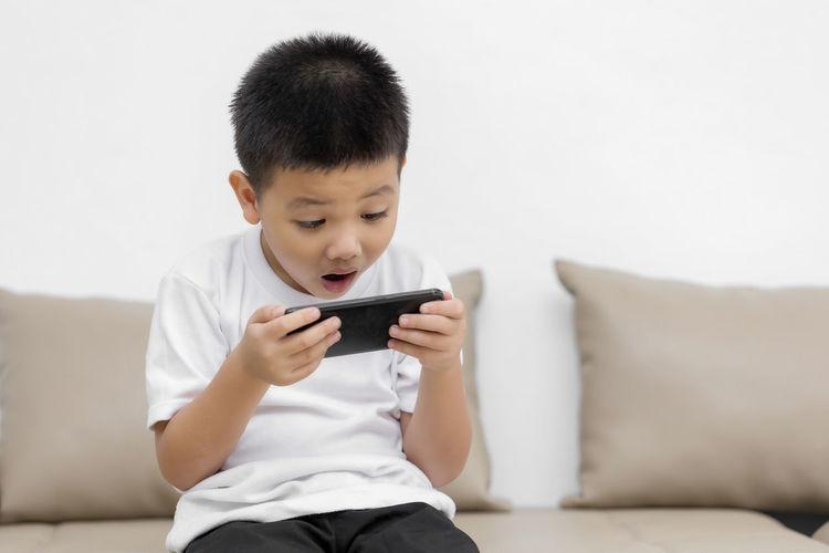 Boy holding mobile phone while sitting on sofa