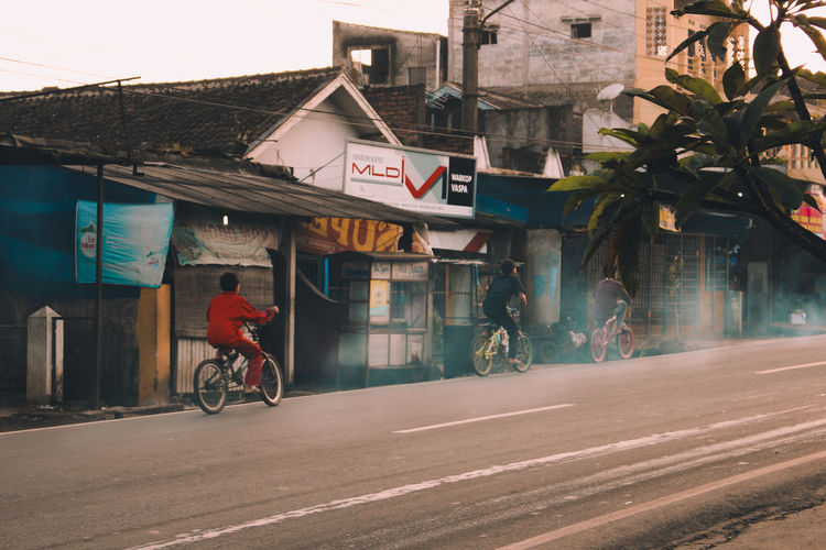 Man riding bicycle on road against buildings in city