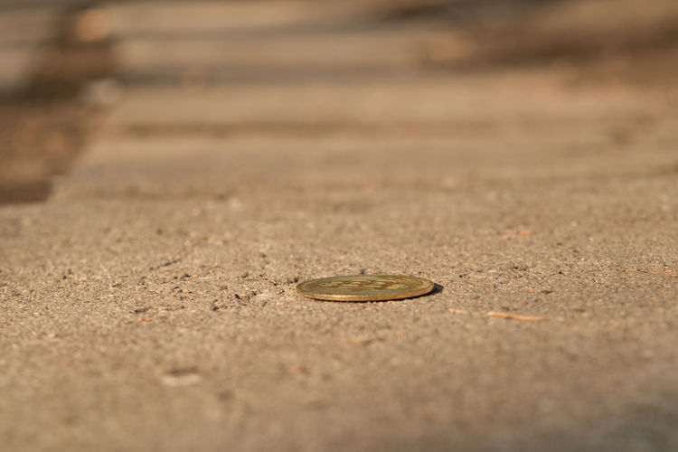 Close-up of coins on sand
