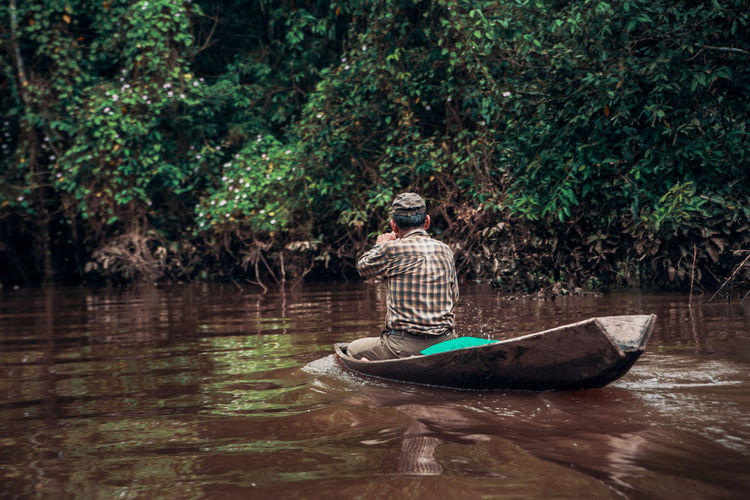 Let's go fishing. Nature Outdoors Non-urban Scene Adventure South America Latin America Jungle Rainforest Amazon Amazonas Nautical Vessel Transportation Rowing Real People Paddling Reflection One Person River Rowboat Mode Of Transportation Waterfront Tree Water Plant Oar