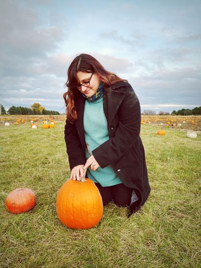 Full length of woman with pumpkin in field against sky