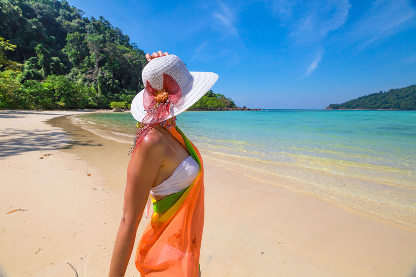 Back of happy and fashionable tourist woman with colorful sarong in turquoise water of Maya Bay famous lagoon of The Beach movie, Phi Phi Leh, Andaman Sea in Thailand Fashionable and happy tourist with sarong and pink wide-brimmed hat making a selfie on tropical famous beach of Nai Harn Beach, Rawai, Phuket, Thailand. Happy tourist enjoys panorama from Sail Rock View Point of kor 8 of Similan Islands National Park, Phang Nga, Thailand, one of the tourist attraction of the Andaman Sea. Happy woman with bikini and shorts, jumping in the air on Ya Nui Beach, a little cove divided by a rocky cape, Phuket, Thailand, Asia. Happy Koh Rok Islands Nui Beach Phang Nga Bay Phuket Thailand Tanning ☀ Thailand Vacations Woman Beach Beauty In Nature Bikini Day Girl Koh Rok Leisure Activity Lifestyles Nature One Person Outdoors People Phang Nga Rawai Real People Rear View Sand Scenics Sea Seascape Shirtless Sky Standing Sunlight Surin Islands Travel Destinations Tree Vacations Water Women Young Adult Young Women