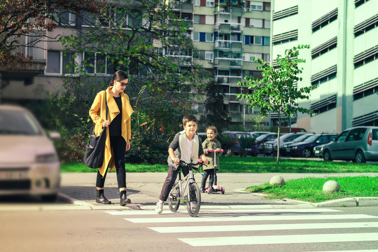 City Child Building Exterior Street Togetherness Boys Women Family Riding Daughter Mother Offspring Son Boy Girl Crossing Crossing The Street Zebra Crossing Crosswalk City Life Attention Parent Safety Real People Full Length
