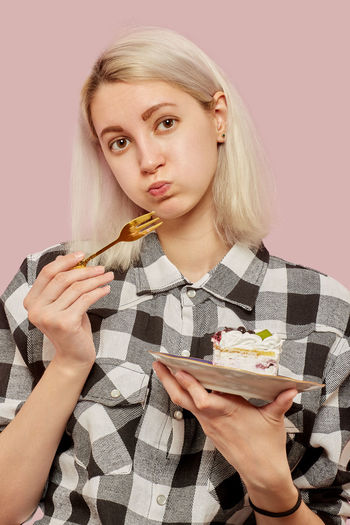 Portrait of young woman eating food against gray background