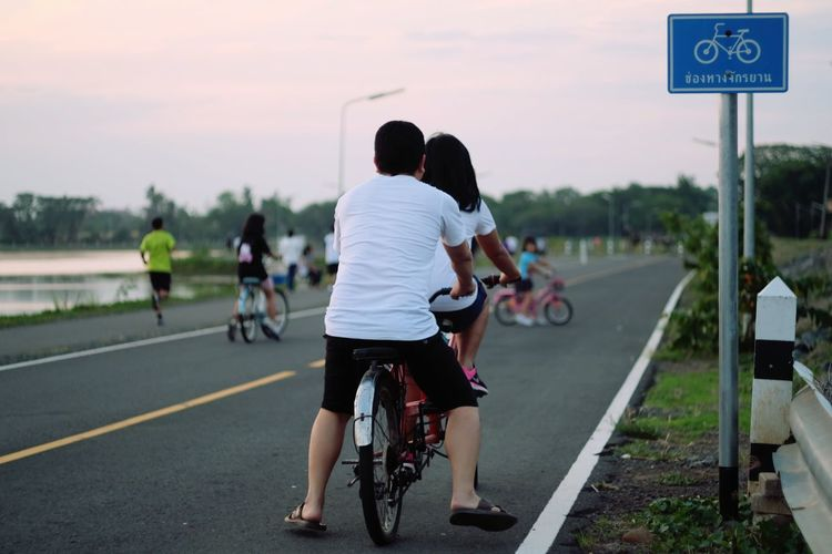 Rear view of couple riding bicycle on road