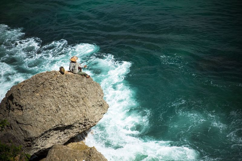 High angle view of man fishing at cliff