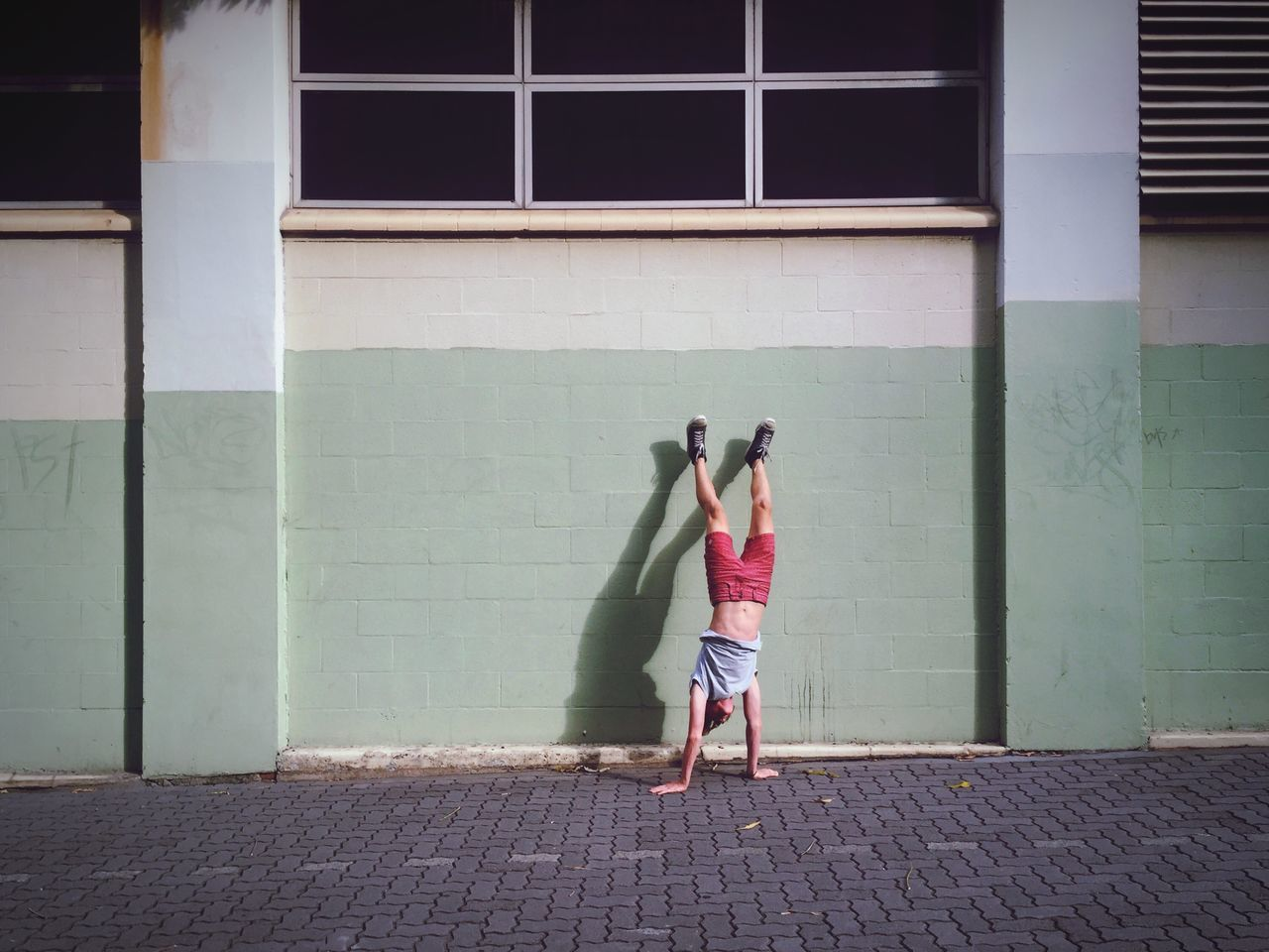 Man doing handstand on footpath against building