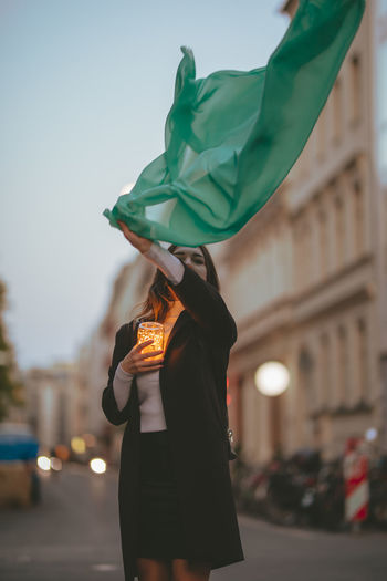 Portrait of beautiful woman moving green scarf while holding illuminated jar in city at dusk