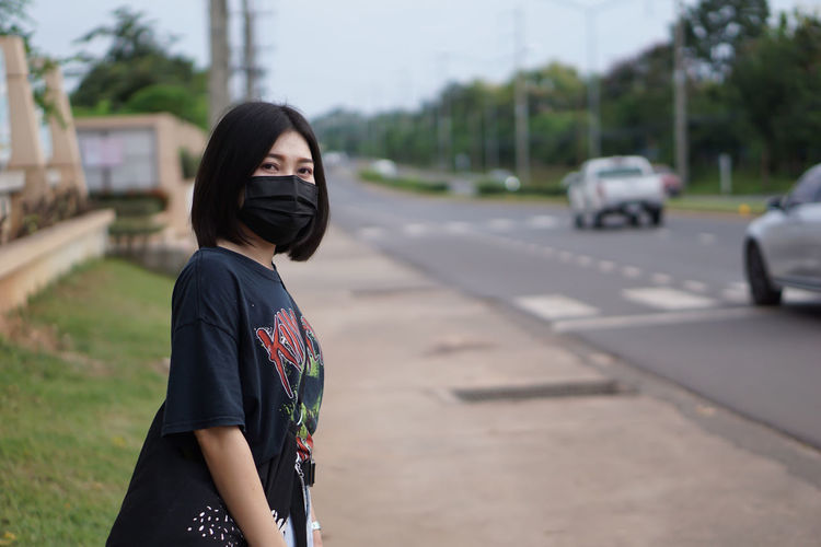 Full length of woman standing on road
