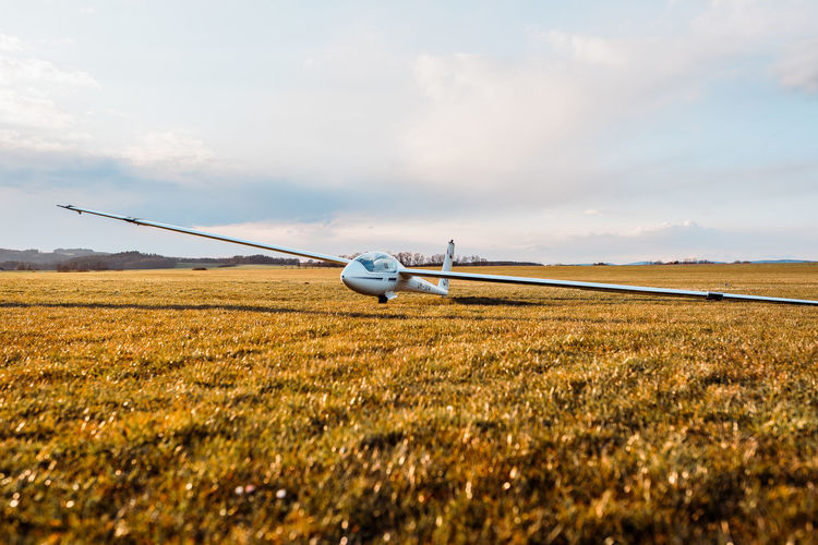 Airplane flying over agricultural field against sky