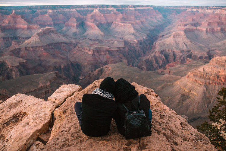 Rear View Of Couple Sitting On Rock Formation At Grand Canyon National Park