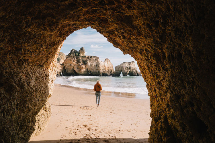 Woman Walking At Beach Seen Through Cave