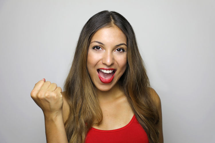 Close-up portrait of cheerful young woman against gray background