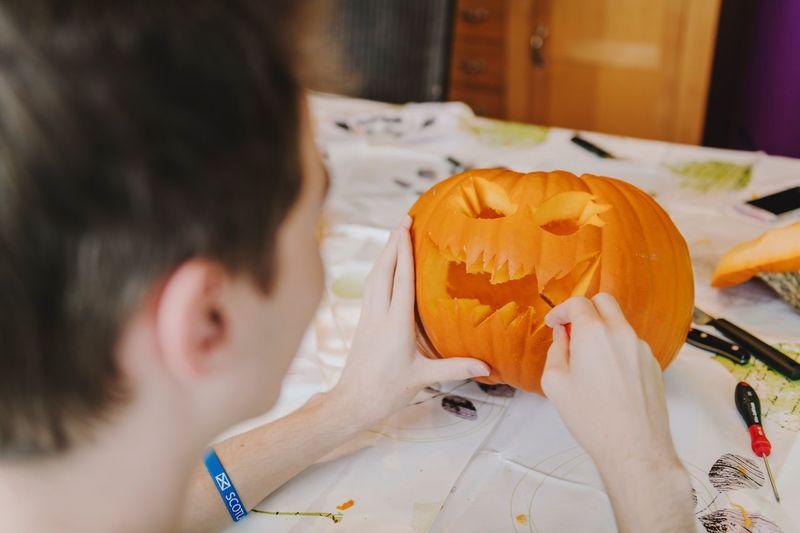 Close-Up Of Baby Boy Carving Pumpkin At Table