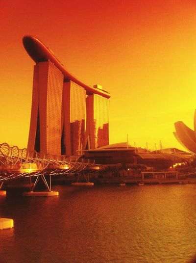 """Singapore's Marina"" Travel Destinations City Travel Cityscape Dramatic Sky Tourism Outdoors Urban Skyline Architecture Skyscraper Bridge - Man Made Structure No People Suspension Bridge Icon Sun Sky Sunset Romantic Sky Fame Amber Singaporestreetphotography"