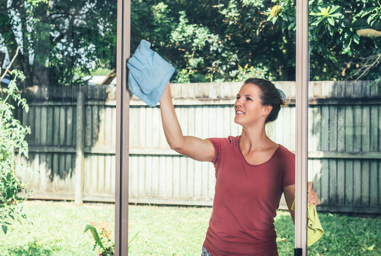 Woman cleaning while standing at yard