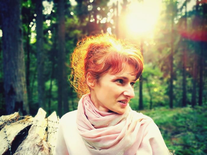 Close-Up Of Thoughtful Woman Standing In Forest During Sunset