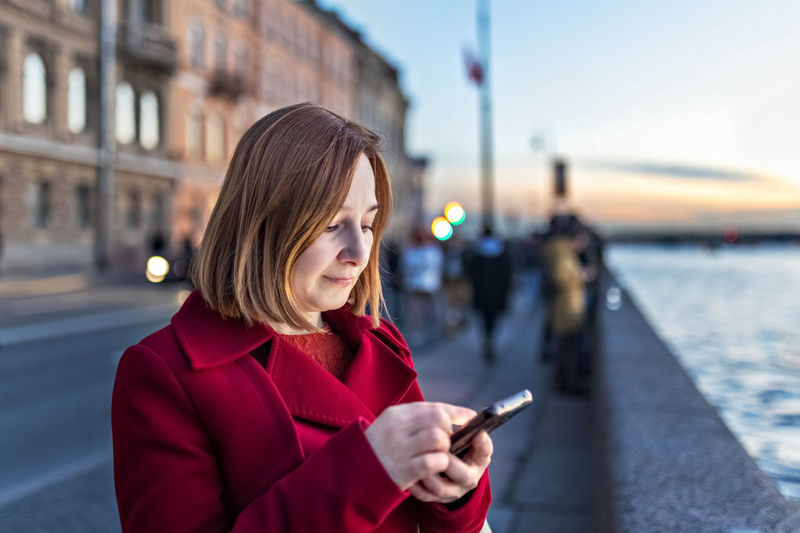 a woman on the embankment of the river in the city, typing text on a smartphone.