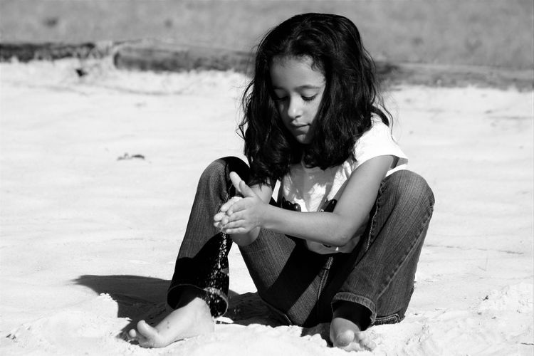 Girl playing with sand at beach