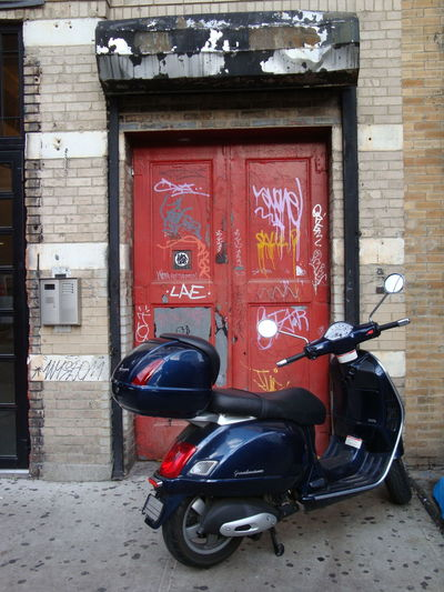 Red bicycle parked against wall