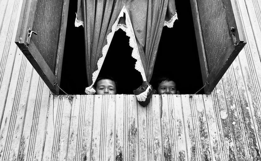 Low angle view of boy peeking though window