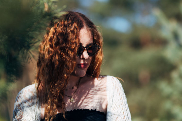 Portrait of young woman with red hairs wearing sunglasses