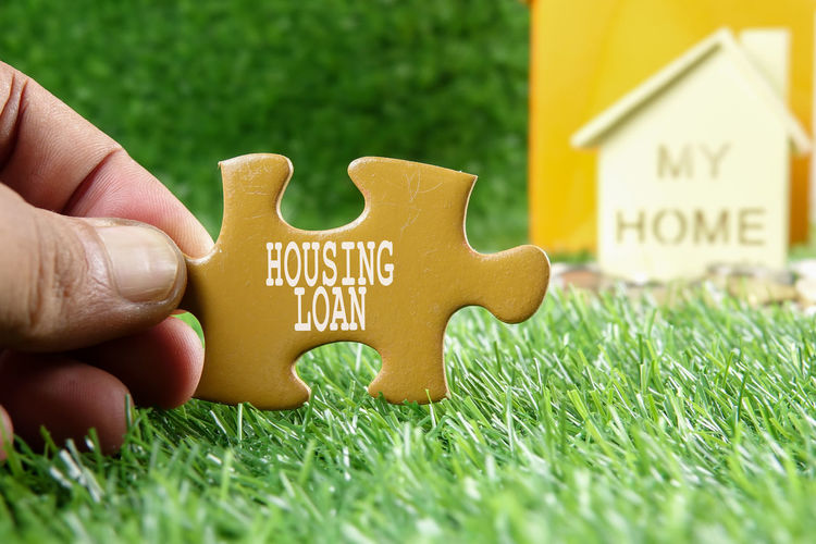 Cropped hand holding jigsaw piece against model house on field