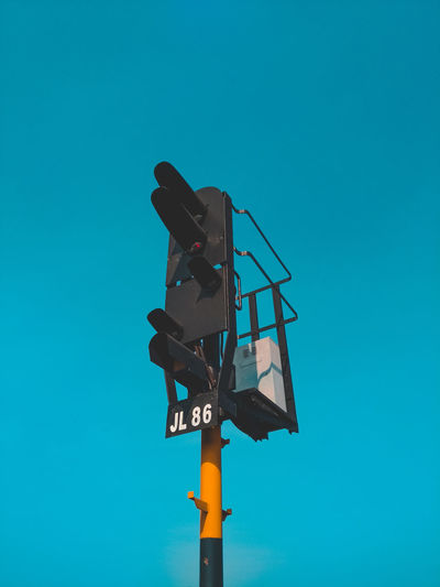 Low angle view of railway signal against blue sky