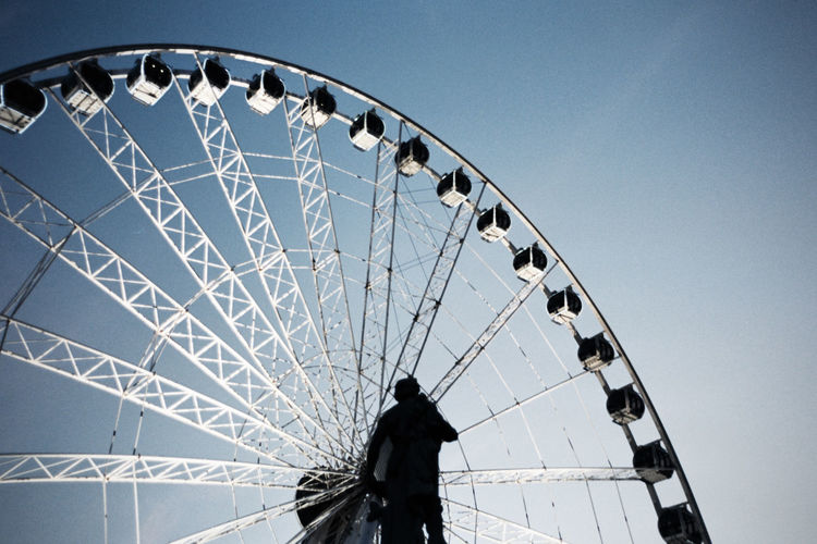 Low Angle View Of Statue In Front Of Ferris Wheel Against Sky