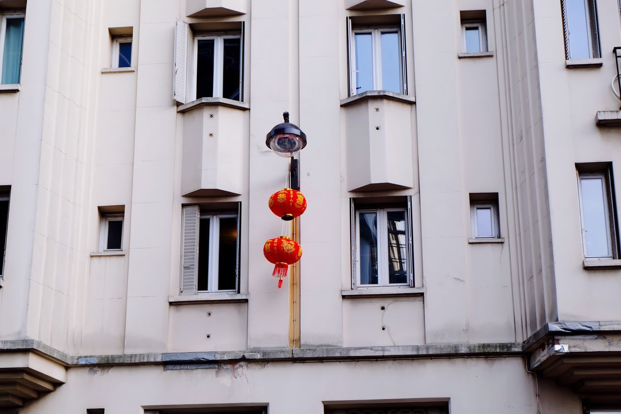 Low angle view of chinese lanterns hanging from street light against apartment building