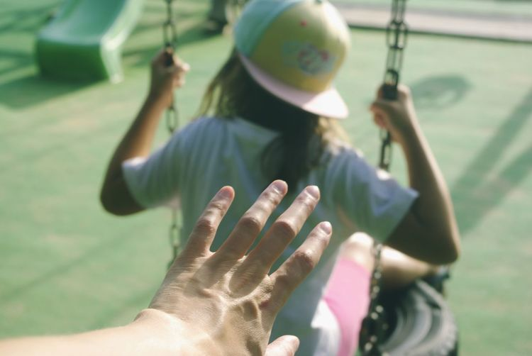 Cropped Hand By Girl Swinging At Park