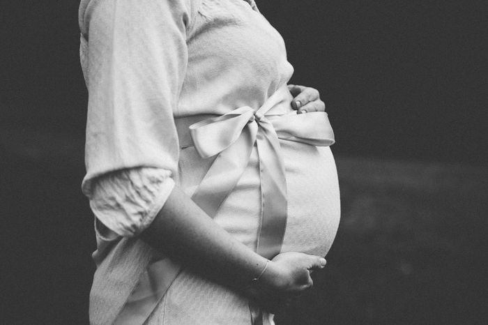 Black and white of the midsection of a pregnant woman with a wrapped belly in profile Babybelly Maternity Belly Black Background Blackandwhite Human Body Part Human Hand Midsection Pregnant Pregnant Belly  Real People Standing Tied Bow Wrapped