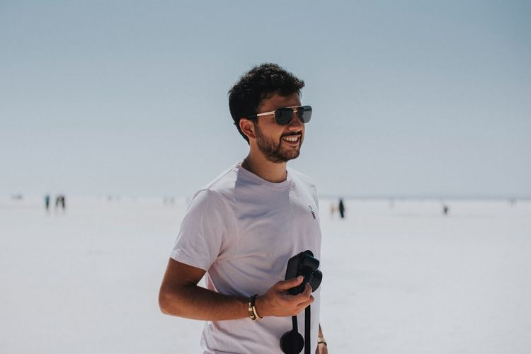 Happy Millenial Tourist Camera Glasses Sunglasses Fashion Young Men Standing Water Beach Casual Clothing One Person Young Adult Nature Sky Outdoors Facial Hair Lifestyles Men A New Beginning This Is Natural Beauty The Modern Professional