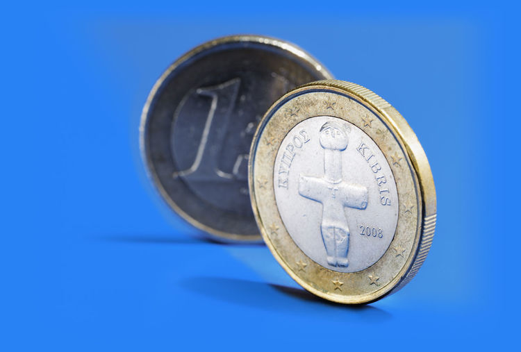 Euro coins from Cyprus on blue background.