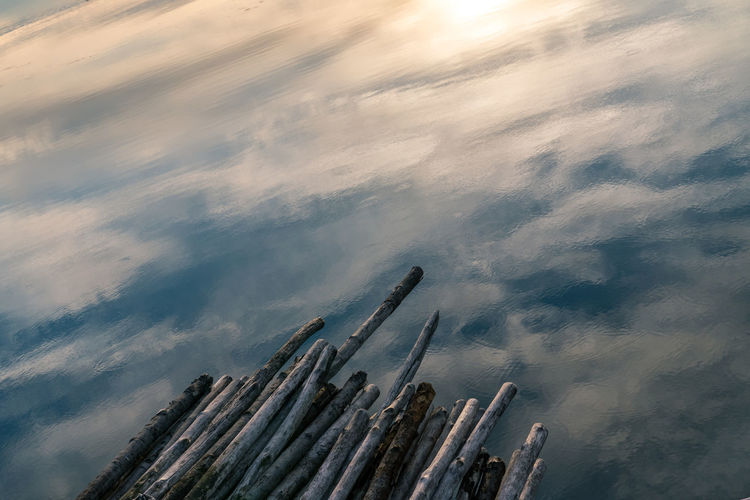 High angle view of wooden post against sky reflected in water