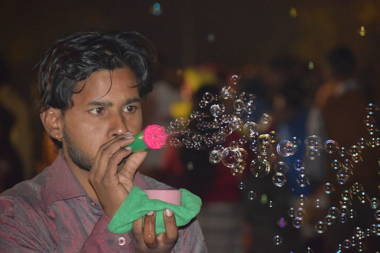 Man blowing bubbles at night