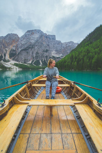Woman Rowing Boat In Lake Against Mountains