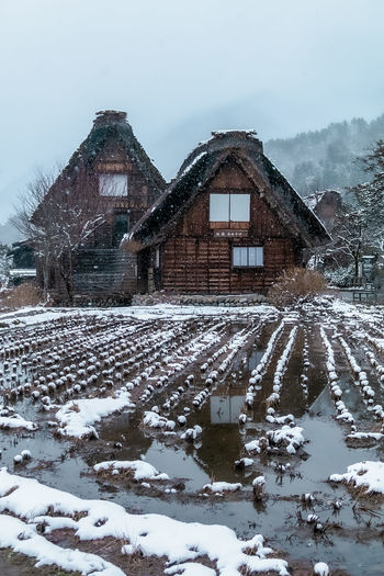 Snow covered field by building against sky