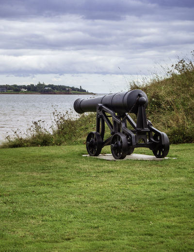 A rifled cannon in Charlottetown, Canada Canada Charlottetown Atlantic Canada City Cityscape Grass Plant Cloud - Sky Water Nature Sky Day Land Black Color Beauty In Nature Field Green Color No People Technology Outdoors Cannon Landscape Tranquil Scene Tranquility History Heritage Military Travel Destinations Sea Waterfront Seascape View