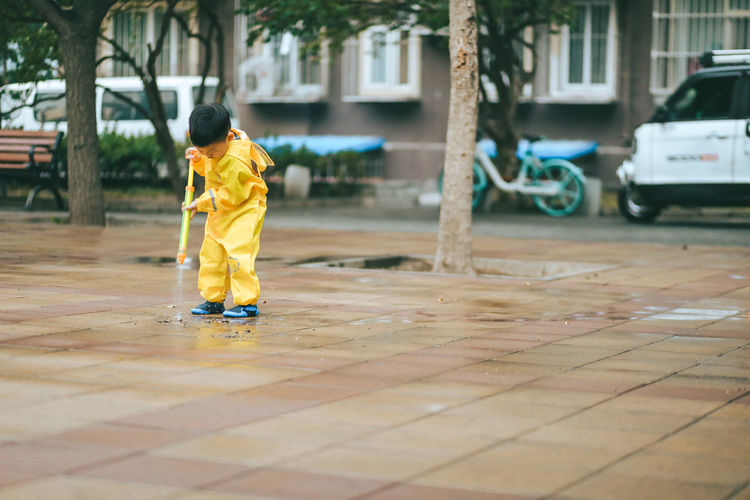 Front view of boy playing in the rain