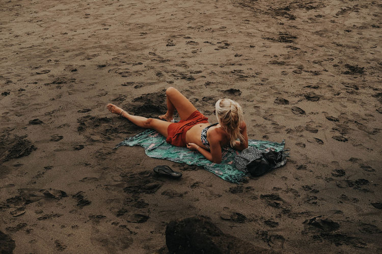 Beach Bikini Day Full Length Go Higher Hairstyle High Angle View Land Leisure Activity Lifestyles Lying Down Lying On Back Nature One Person Outdoors Real People Relaxation Sand Swimwear Women Young Women