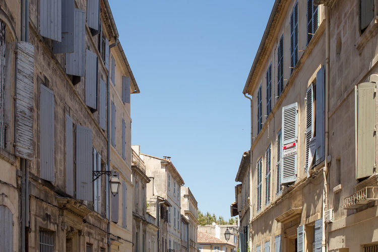 High section of buildings in the Old town, Arles, France Architecture Blue Building Exterior Building Story Built Structure City Clear Sky Day Façade High Section Low Angle View No People Old Town Outdoors Sky Tourism Travel Destinations Window