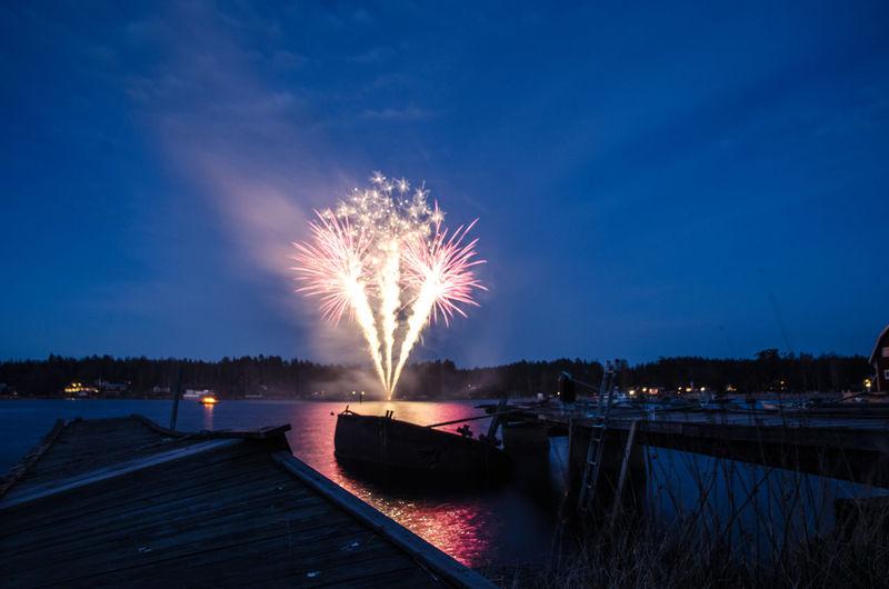 Firework display over river against sky