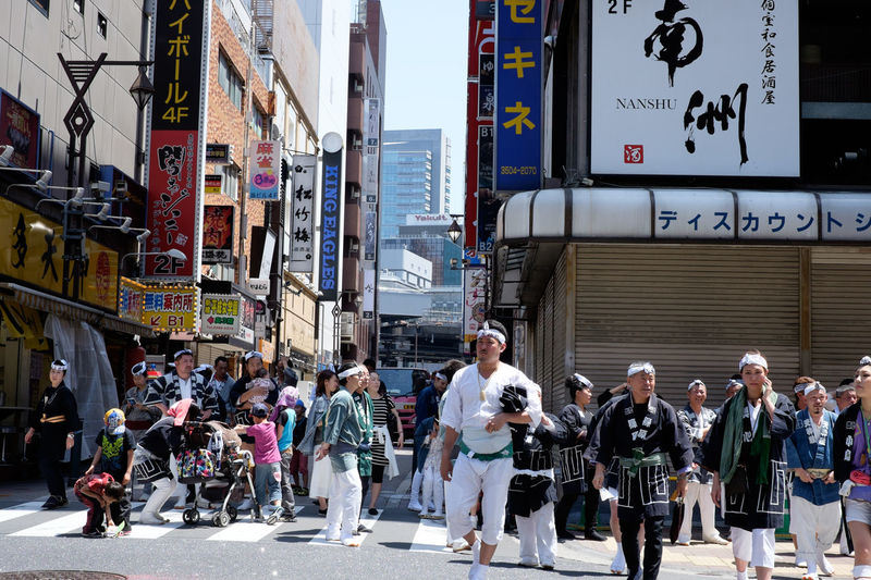 People on street in city during mikoshi festival