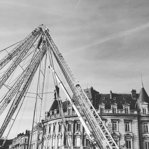 Low angle view of amusement park ride against historic building in city
