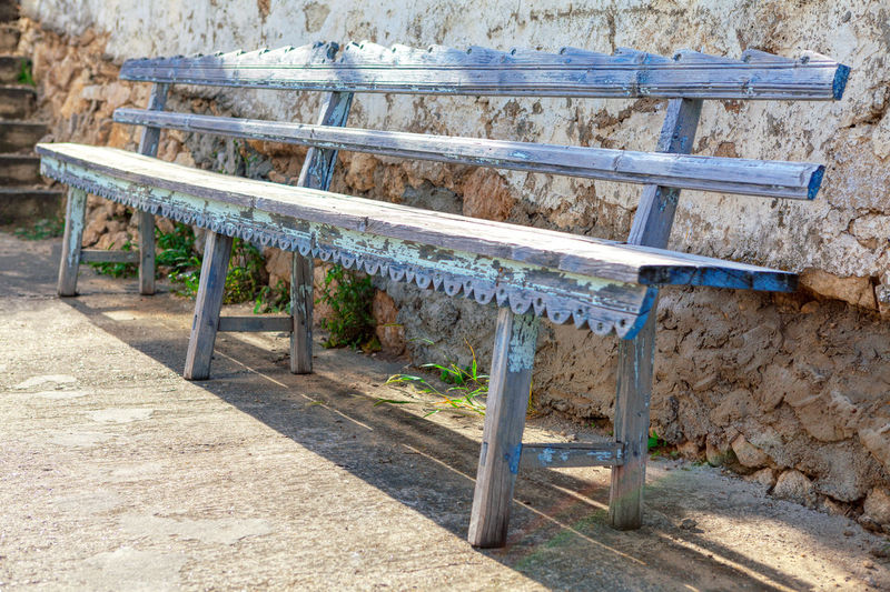 Empty bench in park against building