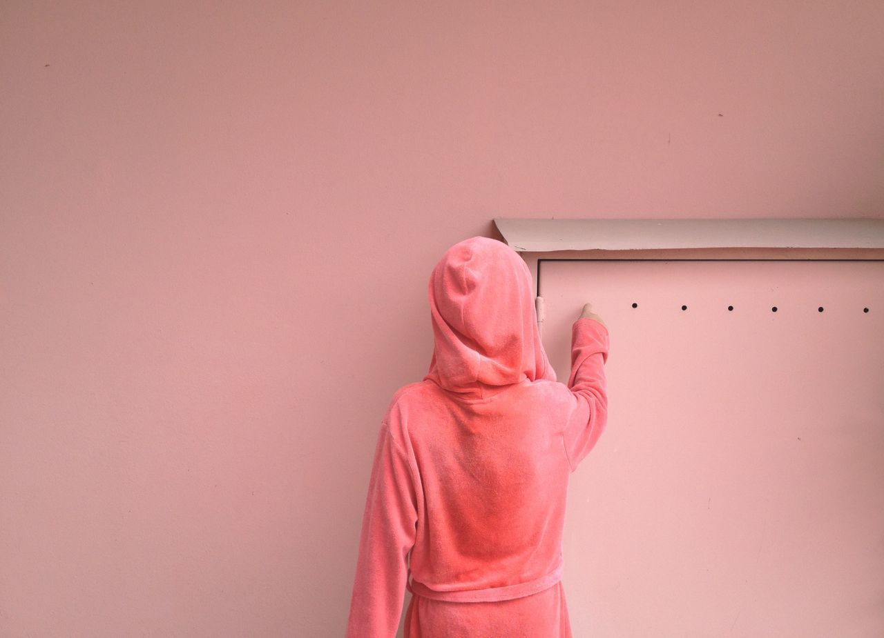 Rear view of woman wearing hooded shirt touching hole on door