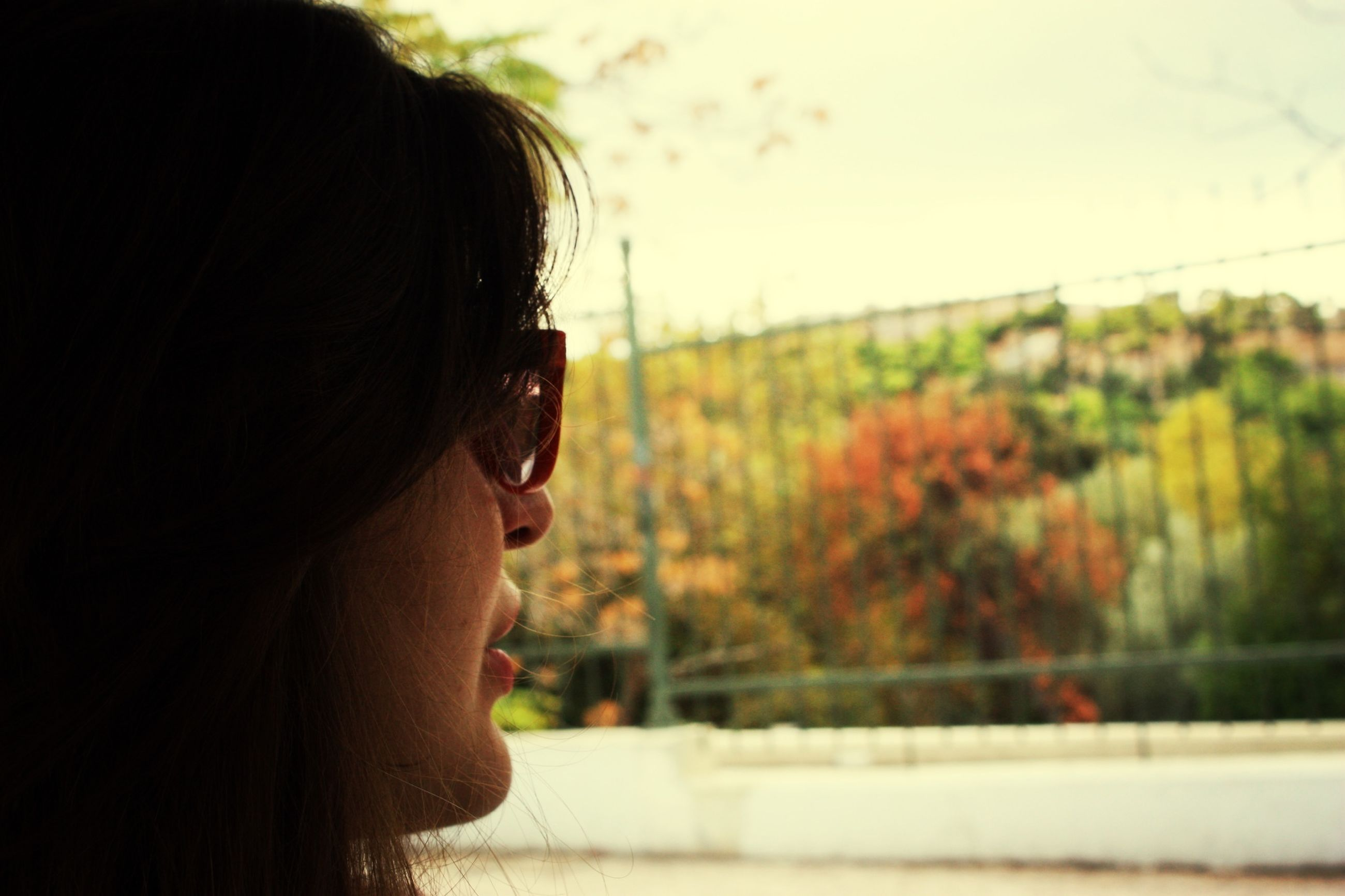 headshot, focus on foreground, lifestyles, leisure activity, person, close-up, young women, young adult, long hair, contemplation, looking away, side view, head and shoulders, brown hair, human face, sky, tree