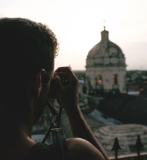Man photographing cathedral at granada department